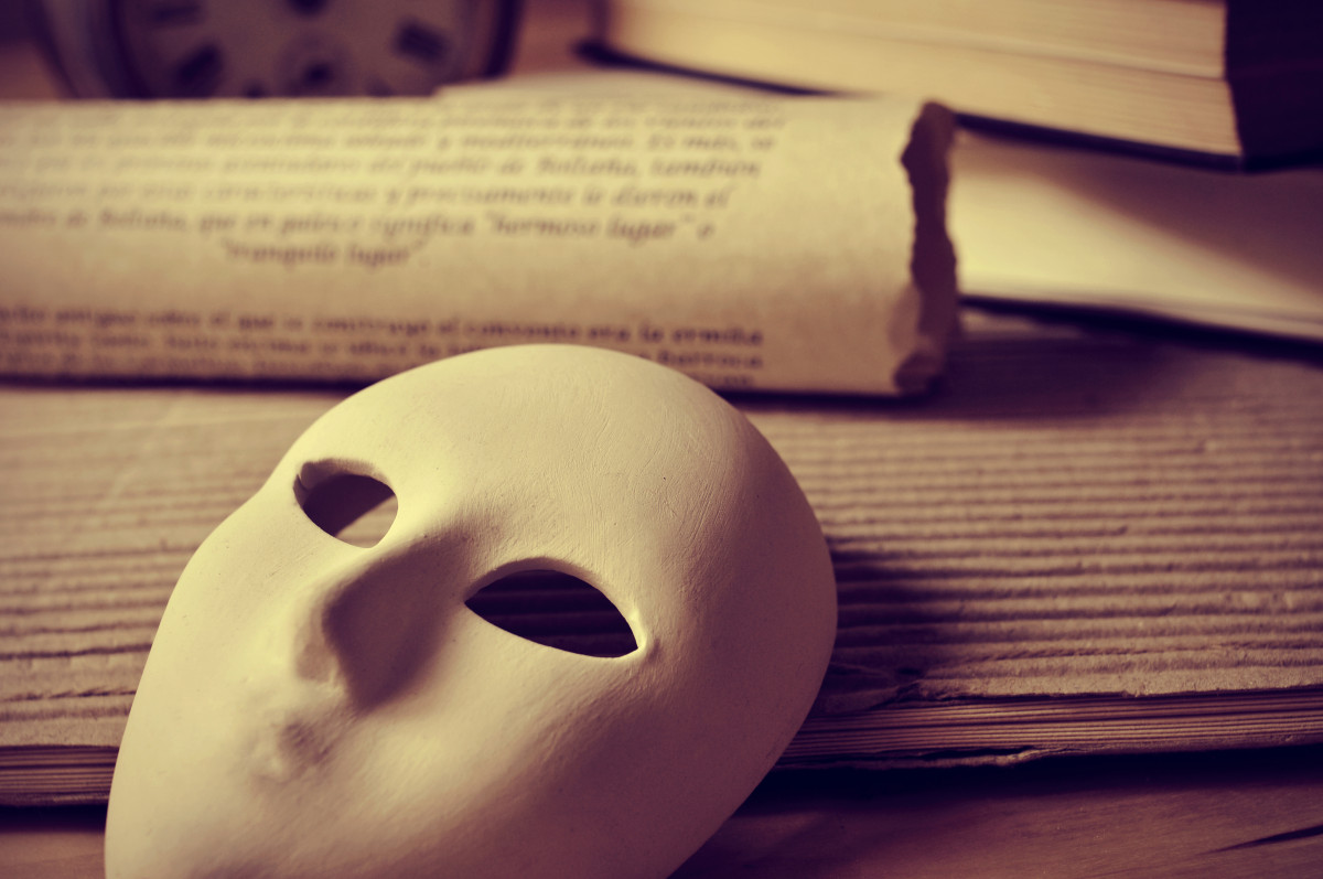 a pile of books and a mask, depicting the concept of playwriting and performing arts